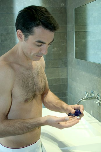 IN*Portrait Valéry torse nu appuyant sur bombe de crème pour contour des yeux : Stock Photo