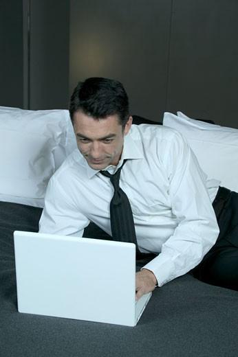 IN*Valery allongé sur lit, travaillant sur ordinateur portable, chemise blanche, cravate noire : Stock Photo