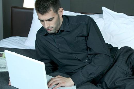 IN*Jeune homme travaillant sur ordinateur portable, allongé sur lit, chemise et pantalon gris : Stock Photo