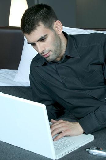 IN*Jeune homme travaillant sur ordinateur portable, allongé sur lit, chemise grise : Stock Photo