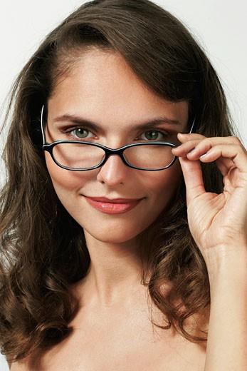 Stock Photo: 1606-25116 IN*Portrait jeune femme brune posant souriante, regardant par dessus ses lunettes de vue(Iléna)