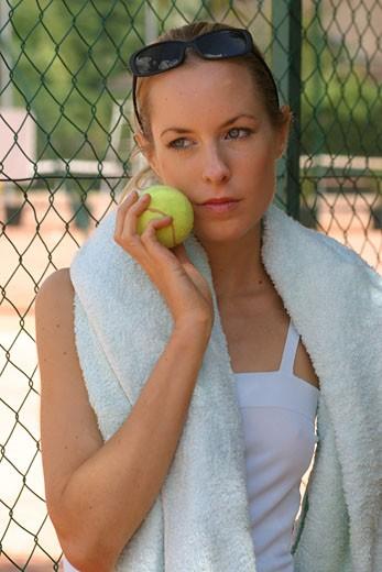 IN*Portrait Sophie pensive, serviette sur les épaules, balle de tennis sur la joue, lunettes de soleil sur les cheveux : Stock Photo