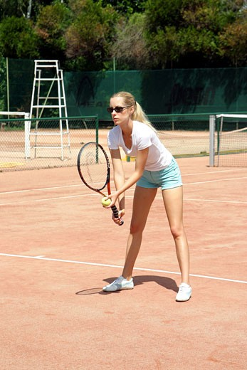 Stock Photo: 1606-25673 IN*Sophie jouant au tennis, short bleu et tee-shirt blanc, lunettes de soleil