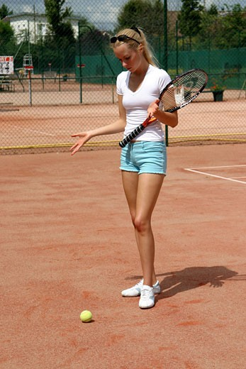 IN*Sophie debout sur court de tennis, regardant balle sur le sol, short bleu et tee-shirt blanc, lunettes de soleil sur les cheveux : Stock Photo