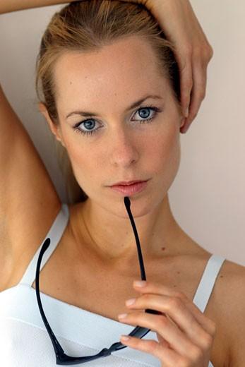 Stock Photo: 1606-25681 IN*Portrait Sophie posant, main sur les cheveux, tenant lunettes de soleil, débardeur blanc