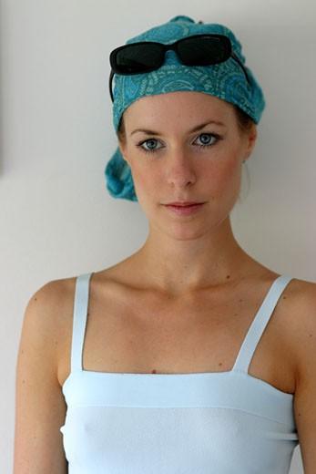 IN*Portrait Sophie pensive, débardeur blanc, lunettes de soleil sur foulard bleu : Stock Photo