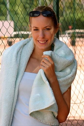 Stock Photo: 1606-25697 IN*Portrait Sophie posant souriante, serviette sur les épaules, lunettes de soleil sur la tête, débardeur blanc, court de tennis en arrière-plan