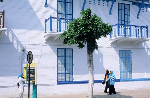 Stock Photo: 1606-27090 Egypt, Port Said, Port Fouad, blue and white house facade of the Suez Canal company, balcony, women on sidewalk