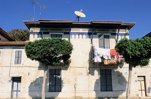 Egypt, Port Said, Port Fouad, house facade of Suez canal company, clothes, parabolic dish, trees : Stock Photo