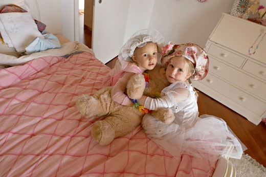 Stock Photo: 1606-27257 Plunging view on two girls posing, with hats and princess dresses, hugging teddy bear, on a bed