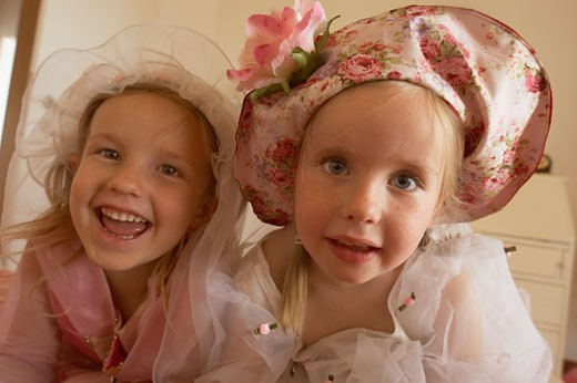 Stock Photo: 1606-27258 Portrait two girls posing smiling, hats and princess dresses