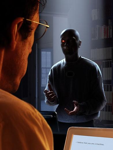 """IN*Homme de dos travaillant sur ordinateur, inscriptions """"I believe that you are a machine"""", """"homme-robot"""" avec oeil rouge dans la pénombre : Stock Photo"""