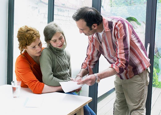 Stock Photo: 1606-27365 Man showing school report sitting on woman's knees