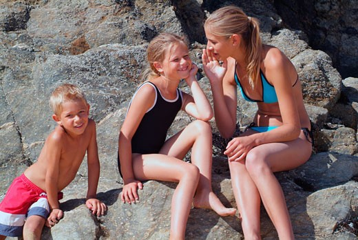 Girl with swimsuit sitting on a rock, whispering into the girl's ear, boy posing beside them : Stock Photo