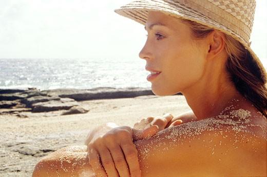 Stock Photo: 1606-28581 Portrait thoughtful woman sitting on beach
