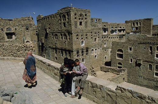 Yemen, Tulah fortified village, children reading sitting on low wall, woman : Stock Photo