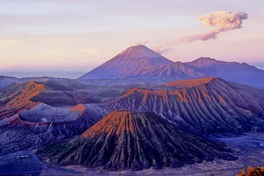 Indonesia, Java, Mount Bromo and Tengger Caldeira, the Semeru volcano erupting in the background, sunrise : Stock Photo
