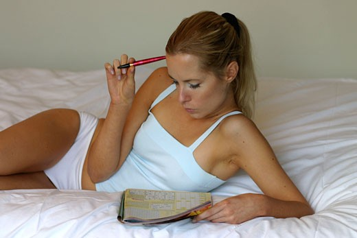 Woman lying down on bed, doing crosswords : Stock Photo