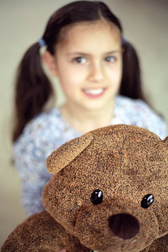 Portrait girl smiling, teddy bear in the foreground : Stock Photo