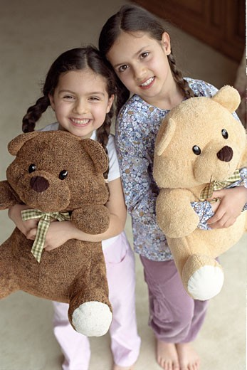 2 girls smiling, each one holding a soft toy : Stock Photo