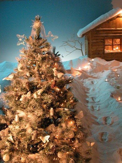 Christmas tree, candles-bordered path to a small chalet, foot prints : Stock Photo