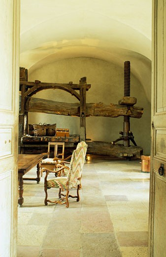 France, Burgundy, Côte-d'Or, château de Pommard, door open to room with ancient wine press, armchairs around table : Stock Photo