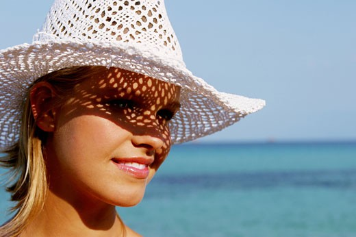 Portrait woman smiling, seaside, white hat : Stock Photo
