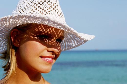 Stock Photo: 1606-32205 Portrait woman smiling, seaside, white hat