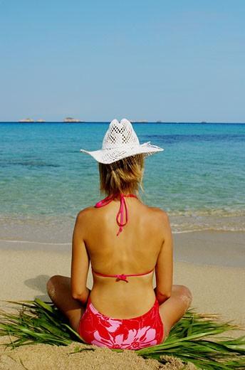 Stock Photo: 1606-32220 Woman sitting on palm leaf, on beach