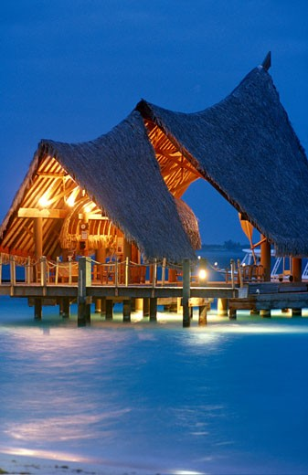 Polynesia, lighted stilted house, blue sea : Stock Photo