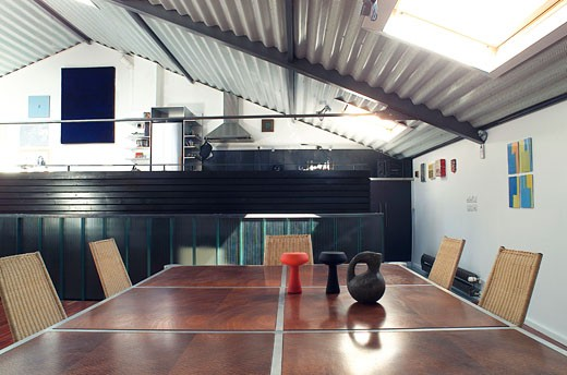 Loft interior, dining room table in the foreground, mezzanine with kitchen in the middle distance : Stock Photo