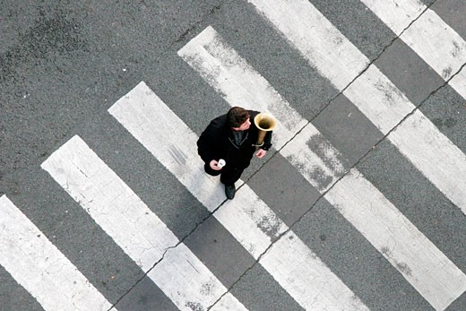 Man dressed in black, crossing the street, holding ice-cream cone and cornet player : Stock Photo