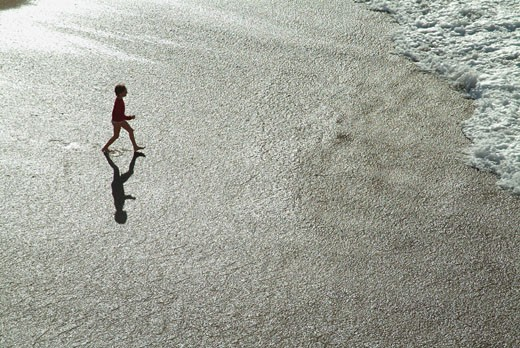 Stock Photo: 1606-35346 Child on the beach, walking to the sea, backlighting