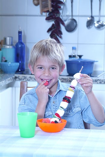 Kitchen, boy smiling, eating brochette of sweets : Stock Photo