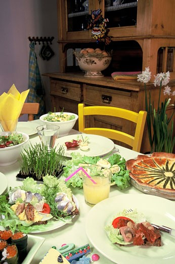 Stock Photo: 1606-36056 Egg-based Easter meal : salads, slices of bread with herring, asparagus quiche, yellow chair, buffet in background