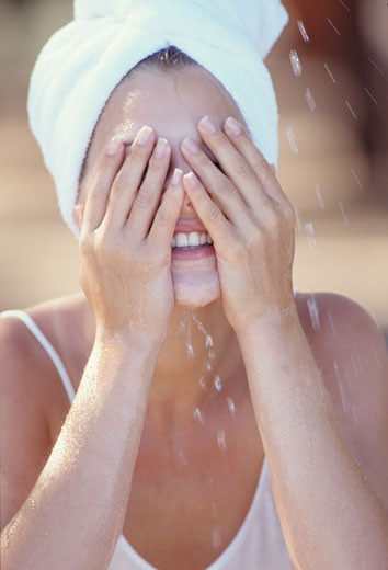 Stock Photo: 1606-37745 Portrait woman, white towel on her head, tank top, spraying her face with water, outdoor, summer