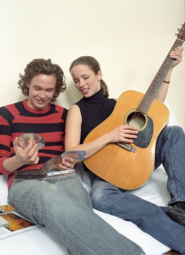 Woman and man smiling, sitting against white wall, her playing guitar, him holding CD : Stock Photo