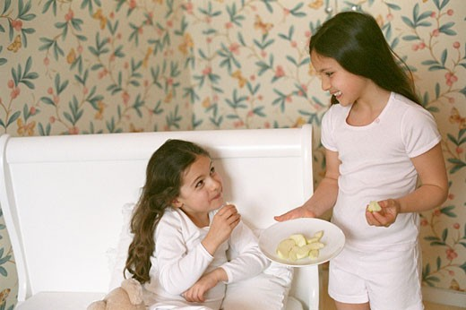Two little girls smiling, in room, one of them aiming apple slice at the other, sitting on the bed : Stock Photo
