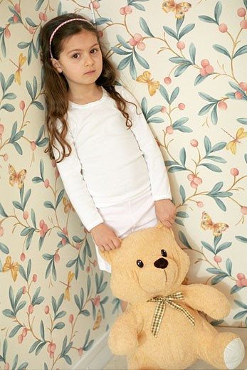 Stock Photo: 1606-37773 Little girl posing, standing in a room, holding big teddy bear on the floor, wallpaper