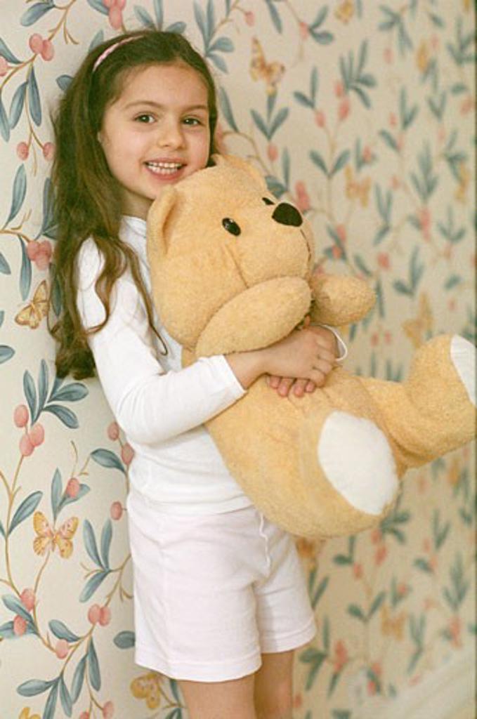 Little girl posing, standing in a room, hugging big teddy bear, wallpaper : Stock Photo