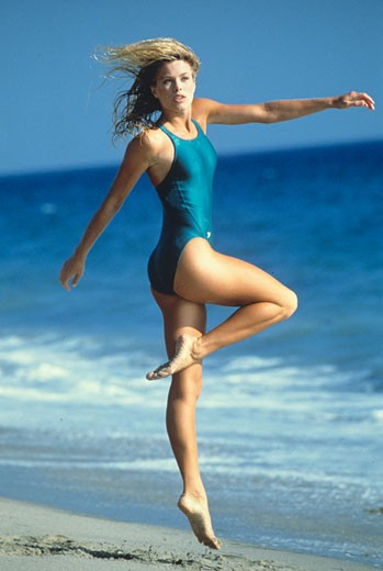 Blond woman, blue swimsuit, jumping on the beach,sea in the background : Stock Photo