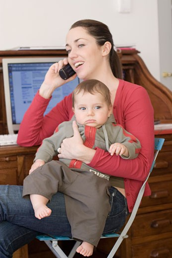 Woman smiling, carrying baby boy on her knees, making a call from her mobile phone, sitting at her desk : Stock Photo