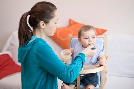 Stock Photo: 1606-37941 Woman feeding little boy, seated in high chair, small plastic pot