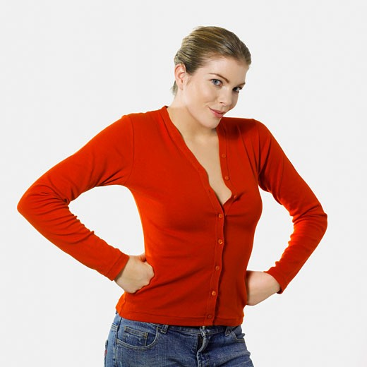 Stock Photo: 1606-38356 Woman posing, smiling, half-open red cardigan, jeans, hands on her hips, white background