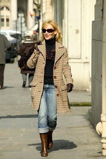 Stock Photo: 1606-38553 IN*Femme blonde souriante, marchant dans la rue, lunettes de soleil, bottes, manteau, sac à main