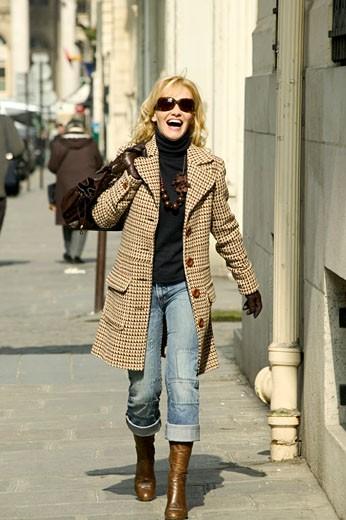 IN*Femme blonde riant, marchant dans la rue, lunettes de soleil, bottes, manteau, sac à main : Stock Photo