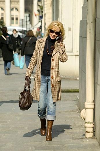 IN*Femme blonde marchant dans la rue en téléphonant avec mobile, lunettes de soleil, bottes, manteau, sac à main : Stock Photo