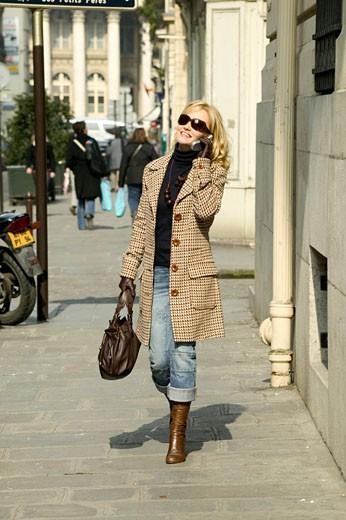 Stock Photo: 1606-38556 IN*Femme blonde souriante, marchant dans la rue en téléphonant avec mobile, lunettes de soleil, bottes, manteau, sac à main