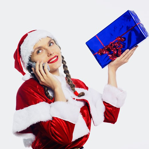 Portrait smiling woman dressed up in Santa Klaus, phoning with cell phone, holding present : Stock Photo