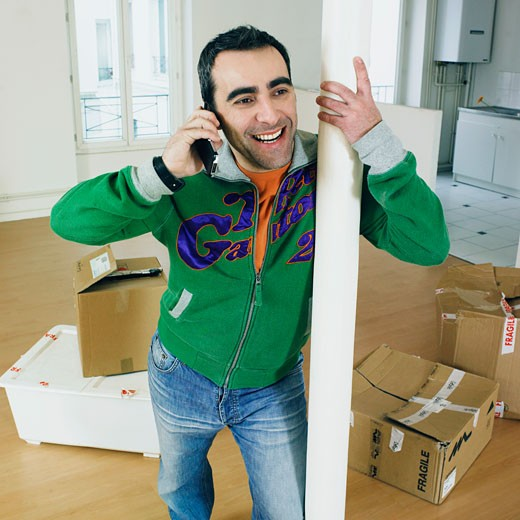 Smiling man phoning with cell phone, standing in empty apartment, removal boxes on parquet, column : Stock Photo